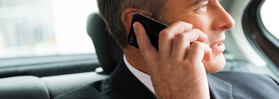 Business Man speaking on the phone in a limosine